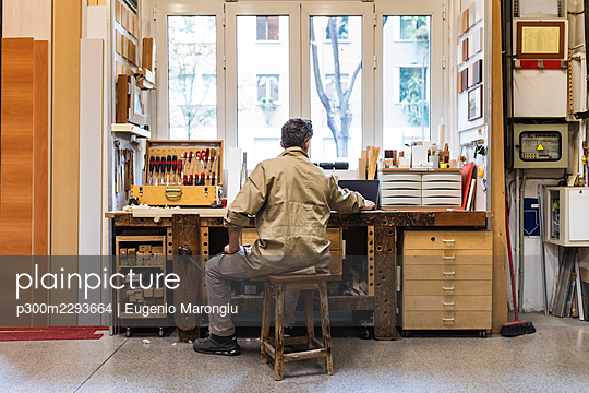 Mature male owner working on laptop at workshop - p300m2293664 by Eugenio Marongiu