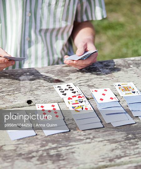 Man playing cards - p956m1044293 by Anna Quinn