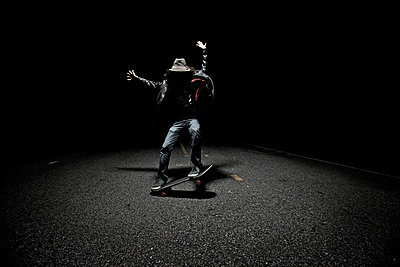 Skateboarder doing tricks in the shadows of the night - p1424m1501147 by Dylan Lucas Gordon
