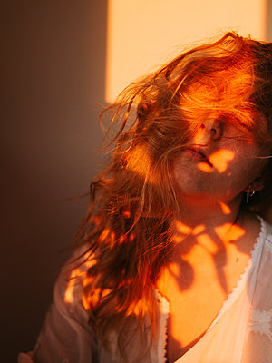 Young woman with long hair takes a nap in the sunlight - p1507m2172000 by Emma Grann
