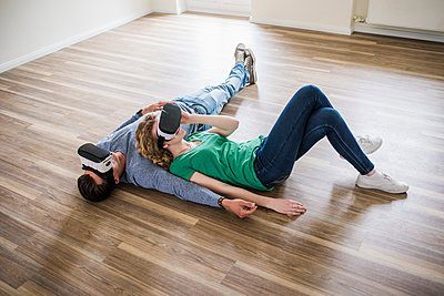 Young couple lying on floor in empty apartment wearing VR glasses - p300m1459814 by Uwe Umstätter