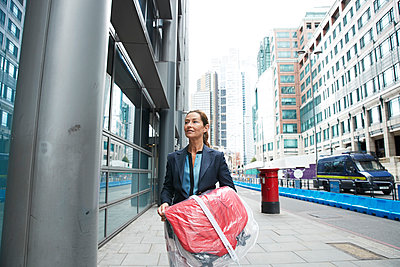 Smiling businesswoman holding shopping clothes while walking on street in city - p300m2226413 by Pete Muller