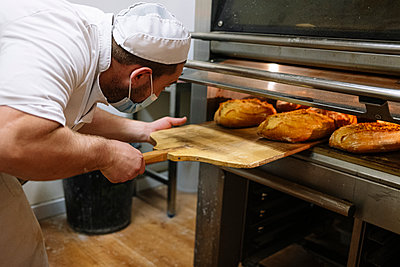 Male baker removing breads from oven in kitchen at bakery - p300m2242878 by Jose Luis CARRASCOSA