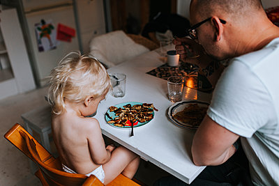 Father and toddler having meal at table - p312m2239735 by Jennifer Nilsson