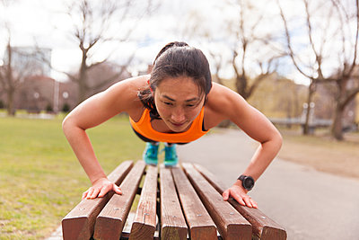 Woman Doing Push-up On The Bench Of The Park - p343m1218165 by Lucie Wicker