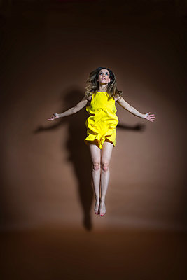Hovering young woman in yellow dress - p427m2063088 by Ralf Mohr