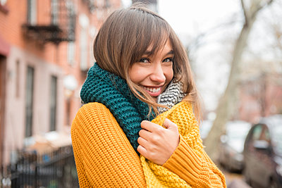 Portrait of smiling Mixed Race woman wearing scarf in city - p555m1231867 by JGI/Jamie Grill