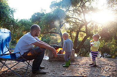 Toddler twins on camping site with father - p924m825984f by Jade Brookbank