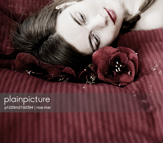 Woman lying next to lilies - p1229m2192394 by noa-mar