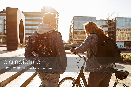 Teenage boy walking with friend holding bicycle in city during sunny day - p426m2018182 by Kentaroo Tryman