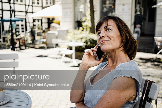 Mature woman using mobile phone in sidewalk cafe - p586m2109114 by Kniel Synnatzschke