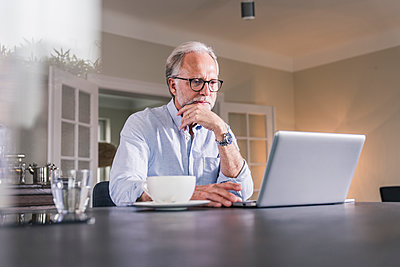 Portrait of mature man sitting at table using laptop at home - p300m1568457 by Uwe Umstätter