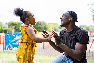 Happy father and daughter playing a clapping game in a park - p300m2155980 by Francesco Buttitta