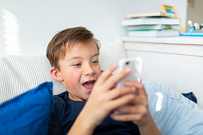 7 year old is in his room playing with his mobile phone at home during the Corona crisis - p300m2180218 von Epiximages