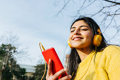 Woman with eyes closed holding smart phone while listening music through headphones against sky in park - p300m2268308 by Xavier Lorenzo