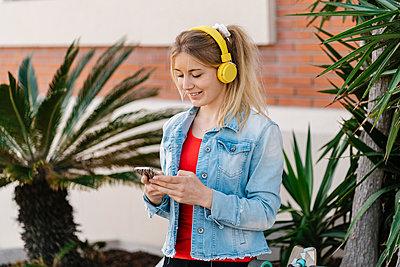 Smiling woman using mobile phone while listening music through wireless headphones - p300m2274906 by Ezequiel Giménez