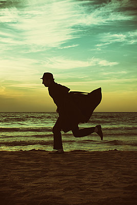 Silhouette of a man running on the beach at sunset  - p794m1508350 by Mohamad Itani