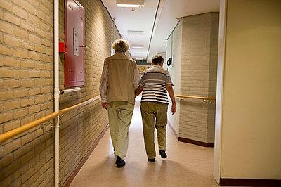 Senior man and his wife walk down the hallway - p8961335 by Sabine Joosten