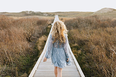 Young woman strolling on coastal dune boardwalk, rear view, Menemsha, Martha's Vineyard, Massachusetts, USA - p924m2058131 by Lena Mirisola