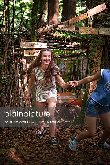 Two girls playing in a hut in the forest - p1007m2220005 by Tilby Vattard