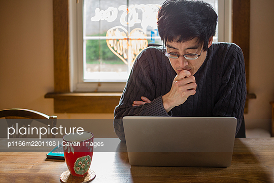 A man sits at a dining room table on computer working from home - p1166m2201108 by Cavan Images