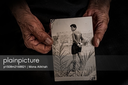Wrinkled hands holding vintage photograph - p1508m2168821 by Mona Alikhah