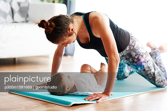 Mother with baby exercising on yoga mat at home - p300m1581669 von gpointstudio