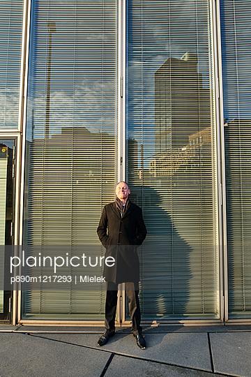 Geschäftsmann lehnt an Glassfassade - p890m1217293 von Mielek