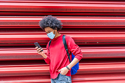 young man with afro hair sending a message from his smartphone - p1166m2255120 by Cavan Images