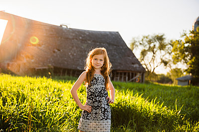 Young girl with red hair standing in tall grass, barn in background. - p1166m2290274 by Cavan Images