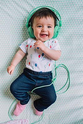 Portrait of happy baby girl with headphones lying on blanket - p300m1459904 by Gemma Ferrando