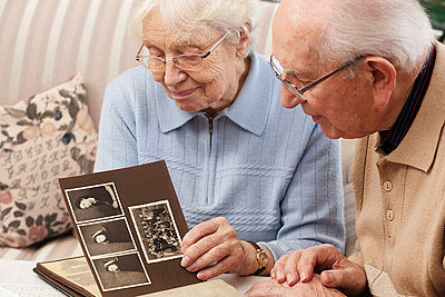 Senior couple watching old photograph album at home - p300m884968f by Ingo Bartussek