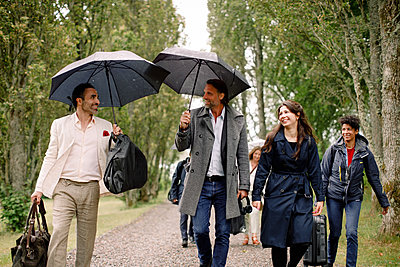Smiling businessmen and businesswomen walking with luggage on footpath - p426m2135402 by Maskot