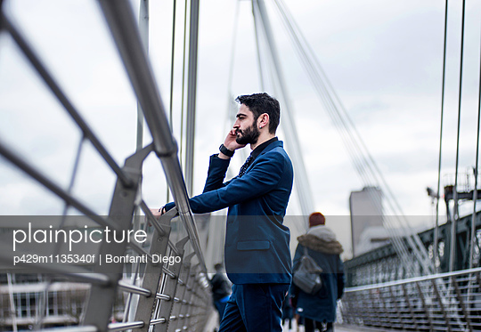 Businessman standing on footbridge talking on smartphone, London, UK - p429m1135340f by Bonfanti Diego