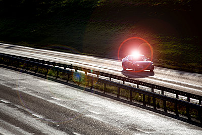 A single car driving down a main highway on a bright autumn morning. - p1057m1510630 by Stephen Shepherd
