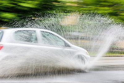 Car splashing water on road - p312m1103588f by Mikael Svensson
