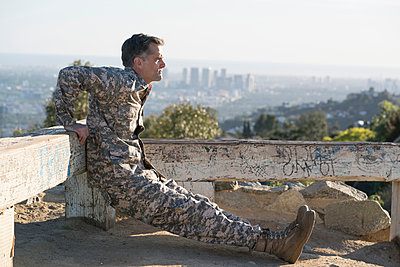 Soldier wearing combat clothing doing reverse push up, Runyon Canyon, Los Angeles, California, USA - p924m1422792 by Raphye Alexius