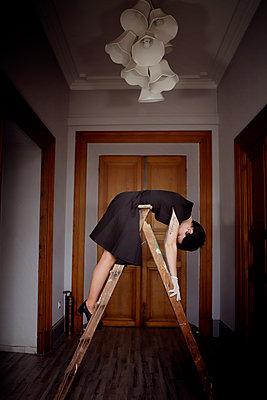Woman in black dress on a ladder - p1105m2244898 by Virginie Plauchut
