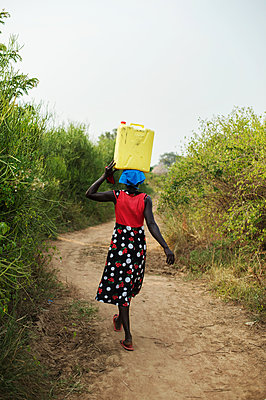 Africa, Uganda, Woman carrying water canister on her head - p1167m2283480 by Maria Schiffer
