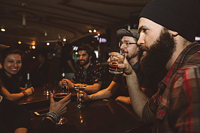 Male millennial hipster drinking whiskey in bar, listening to friends - p1192m1567128 by Hero Images