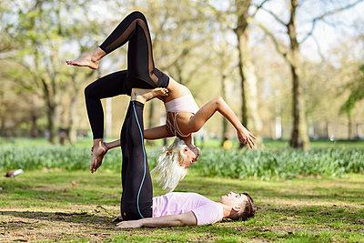 Young couple doing yoga acrobatics in an urban park - p300m2103178 by Javier Sánchez Mingorance