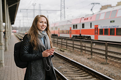 Smiling woman waiting on platform using smartphone and earphones, Vilnius, Lithuania - p300m2154578 by Hernandez and Sorokina