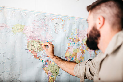 Young man selecting travel destinations on a world map - p300m2219295 by Josep Rovirosa