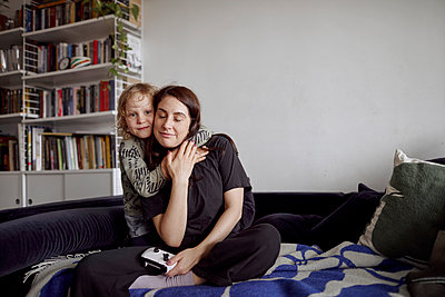 Mother and son hugging on sofa - p312m2285403 by Plattform