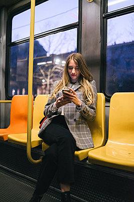 Young woman with long blond hair sitting in train carriage looking at smartphone at dusk - p429m2097886 by Francesco Buttitta