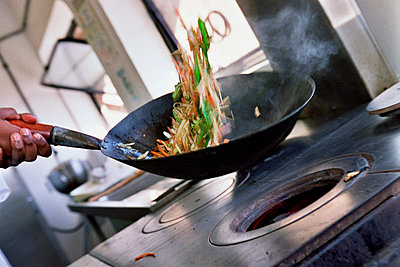 Chef stir-frying vegetables - p92410686f by Image Source