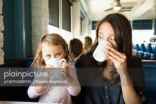 Mother and toddler drinking mugs of coffee in diner - p1427m2283151 by Roberto Westbrook