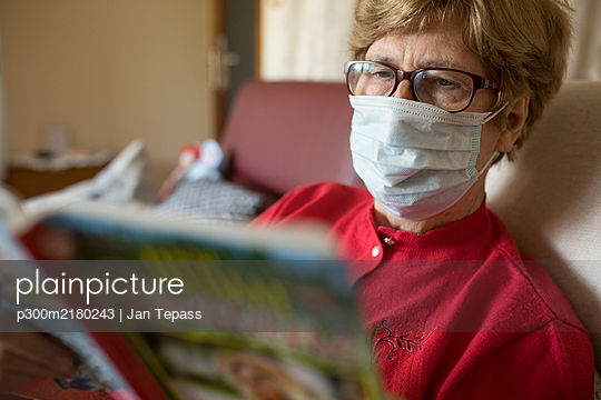 Senior woman reading roman at home and wearing protective mask - p300m2180243 by Jan Tepass