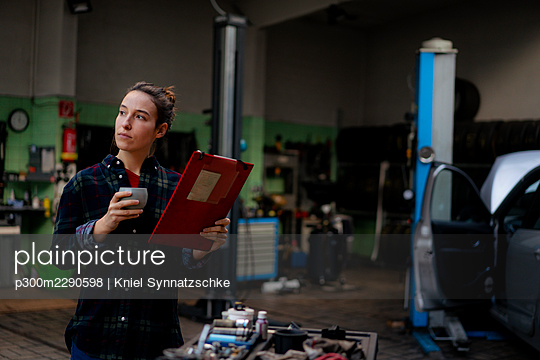 Female mechanic with file having coffee at workshop - p300m2290598 by Kniel Synnatzschke