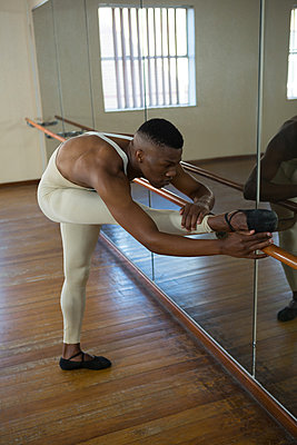 Ballerino stretching on a barre while practicing ballet dance - p1315m1514546 by Wavebreak